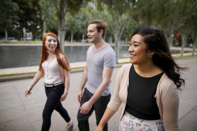 A young man walks between two young women outside as they all talk and smile together.