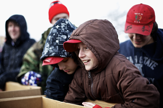 Boy Scouts in winter hats and coats gathering boxes for a food drive.