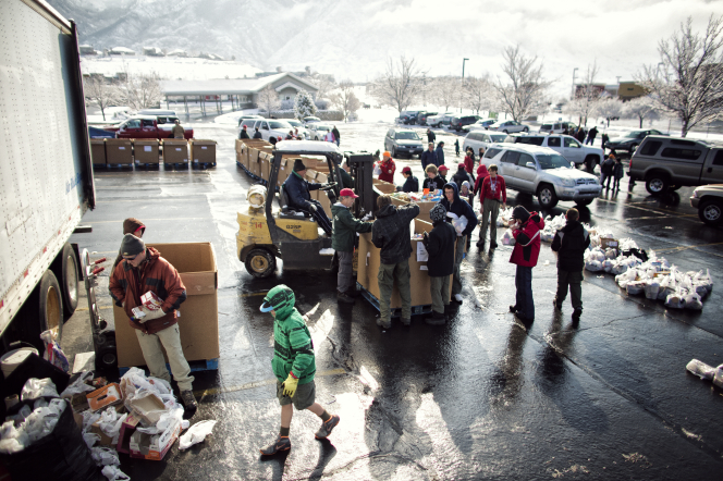 Boy Scouts and leaders standing outside in hats and jackets, sorting food drive items into large cardboard boxes on pallets.