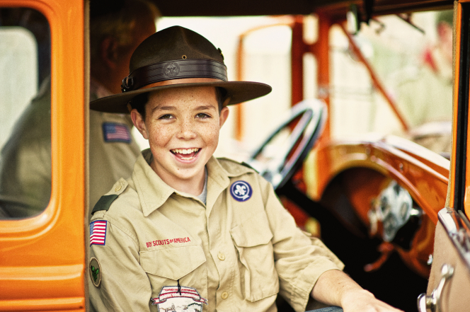 A Boy Scout in his Scout shirt and a black hat, sitting in an old,  remodeled orange truck.