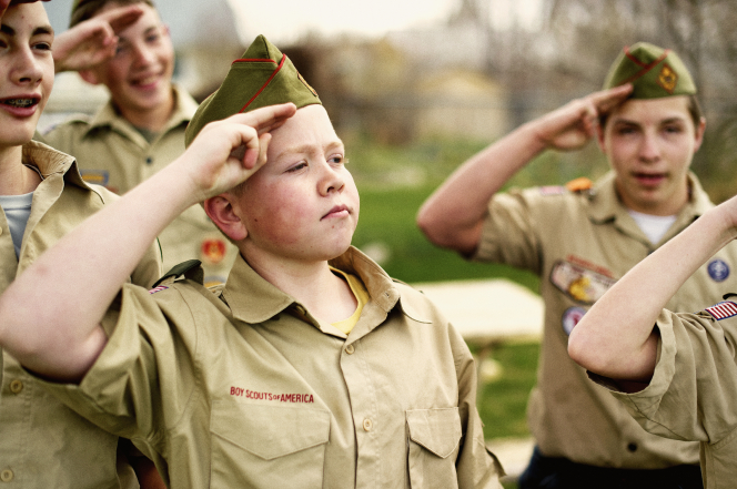 A Boy Scout in his Scout shirt and hat placing two fingers on his forehead to salute the flag.