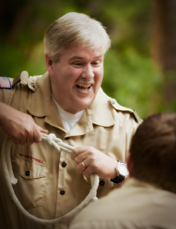 A Scoutmaster standing up and teaching a Boy Scout how to tie a knot with a thick white rope.