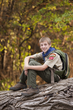 A Boy Scout wearing a Scout uniform, hiking boots, and a backpack, sitting on a fallen tree.