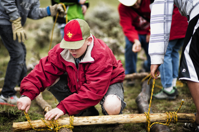 A Boy Scout in a red coat, Scout hat, and worn jeans, leaning down and fastening two wooden poles together by tying a knot.