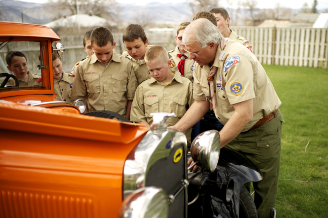 Boy Scouts and their leader gathered around, looking at an old, remodeled orange car.