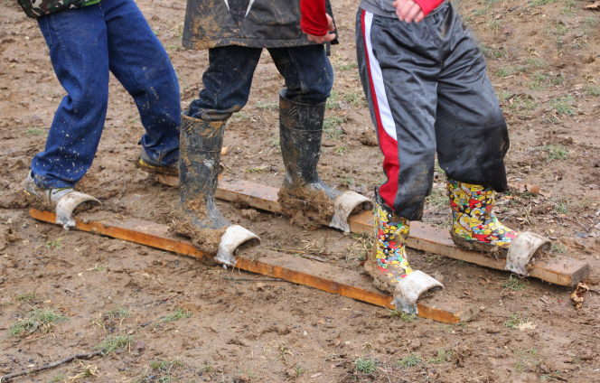 Three Boy Scouts standing and playing a pioneer game by placing their feet in white slots on two wooden boards and walking through the mud.