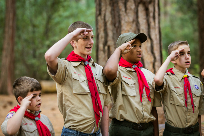 Four Boy Scouts standing in a line at Yosemite National Park and saluting the flag by placing two fingers by their forehead.