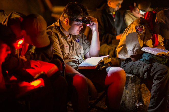 Boy Scouts sitting in the dark and reading scriptures by their headlights at Yosemite National Park.