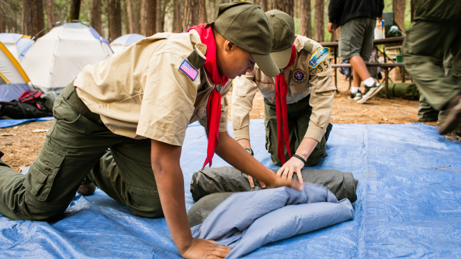 Two Boy Scouts kneeling on the ground and working together to roll up a blue tent.