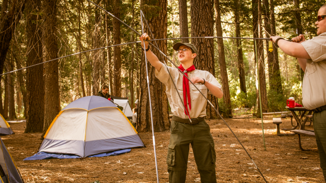 Two Boy Scouts outside building a tent by piecing the poles together at Yosemite National Park.