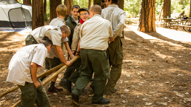 A group of Boy Scouts at Yosemite National Park dragging two wooden poles for a team activity.
