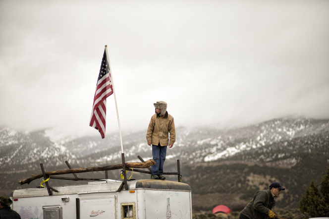 A young man in a winter coat and hat standing on a trailer beside a United States flag.