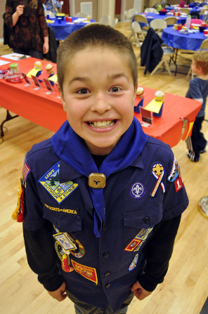 A brown-haired Cub Scout standing and smiling at a Scout banquet inside a cultural hall.
