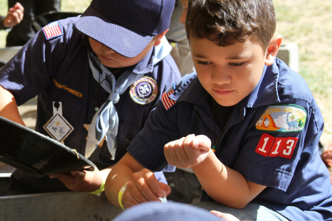 A Cub Scout in a blue hat holding a pan of gold and another Cub Scout holding gold in his hand.