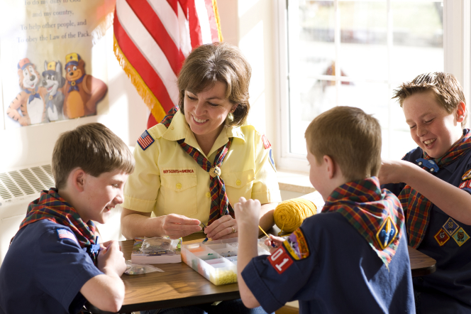 A den mother and three Cub Scouts in Scout shirts sitting around a table and making bead necklaces.