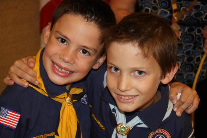 Two smiling brown-haired Cub Scouts with their arms on each other's shoulders.