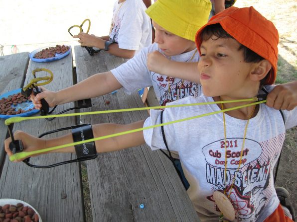 Cub Scouts sitting in the shade at a table and using their slingshots at Scout day camp.