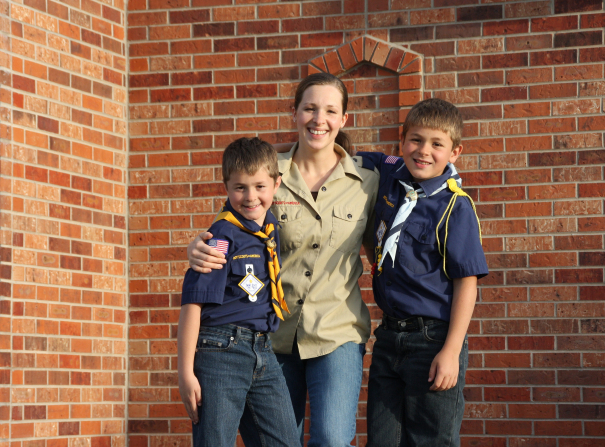 Two Cub Scouts in their Scout shirts standing on either side of their den mother.