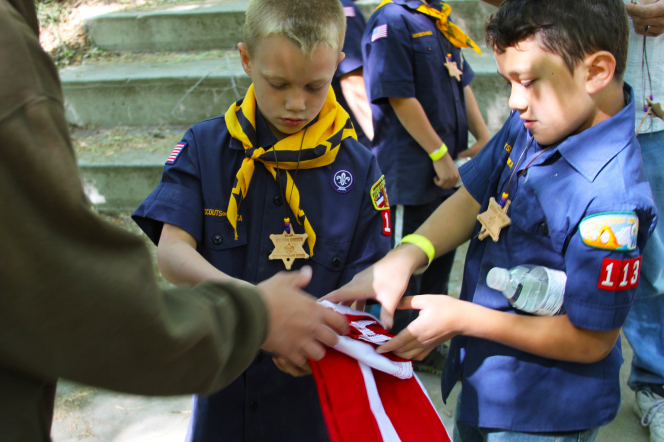 Two Cub Scouts standing outside and folding a red and white flag with the help of a leader.