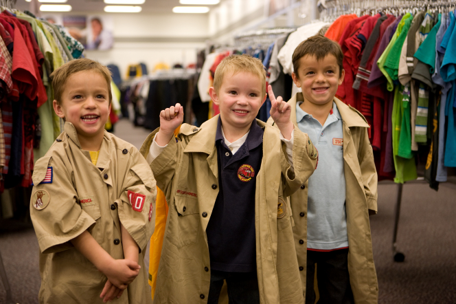 Three smiling young boys wearing Scout shirts over their clothes inside a Deseret Industries store.