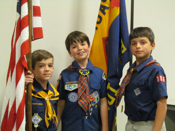 Three young brown-haired Scouts in their Scout shirts, standing by two flagpoles.
