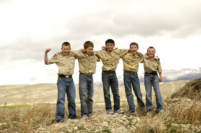 Five Boy Scouts in Scout shirts standing in a line and smiling with their arms over each other's shoulders.