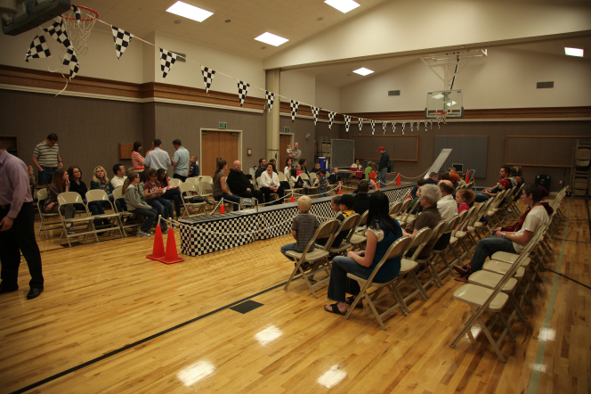 An audience sitting on metal chairs by the race car track at the pinewood derby, waiting for the race to begin.