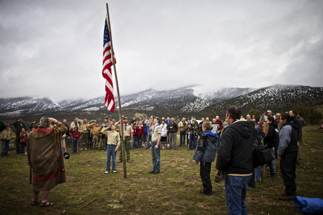 A group of Boy Scouts and an audience standing and saluting the flag while snow falls on mountains in the distance.