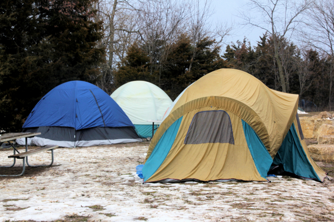 Three large tents placed by a picnic table and trees, with light snow on the ground.