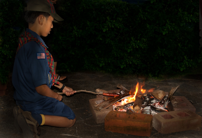 A Cub Scout in Hawaii kneeling on the ground by a campfire and roasting a hot dog on a stick.