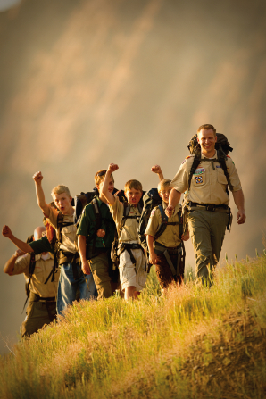 A Scout leader hiking with a group of cheering young men on a trail with the sun shining down on them.