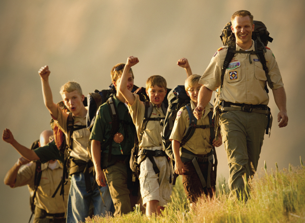 A Scout leader smiling and guiding a group of cheering Boy Scouts up a trail with the sun shining on their backs.