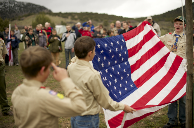 Boy Scouts standing and holding an American flag before beginning to fold it.