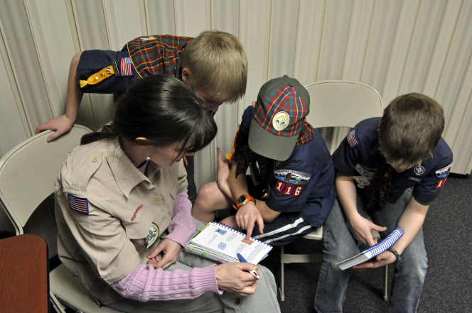 Boy Scouts sitting and reading out of their Scout book with their den mother at the church.