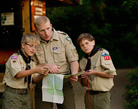 Two Boy Scouts holding compasses, with their leader beside them holding a map.