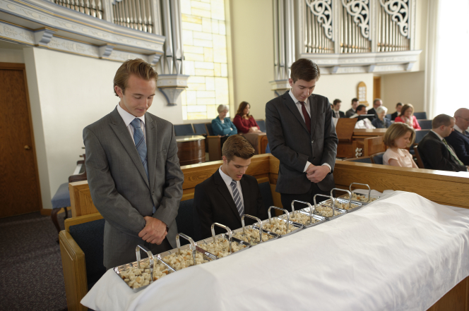 Three young men in suits bow their heads to bless the sacrament bread.