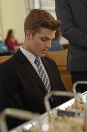A young man in a dark suit and tie kneeling before the sacrament bread to bless it.