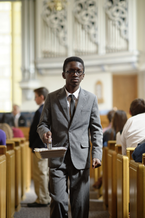 A young man in a suit carrying a sacrament tray along the aisles of a meetinghouse chapel.
