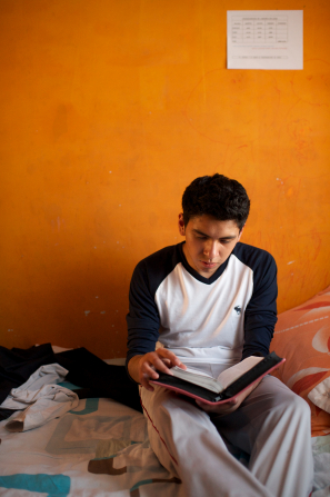 A young man sits on a bed in a room with orange walls and reads from a set of scriptures that is open on his lap.