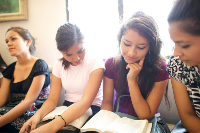Four young women sitting in a classroom at church and studying the scriptures, with the sun shining through a window in the background.