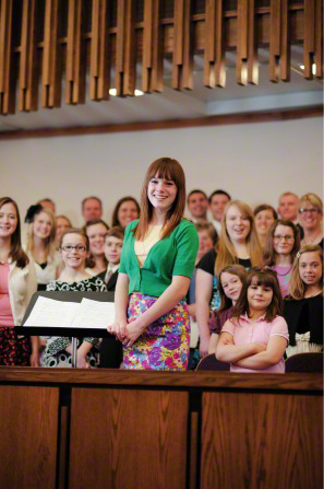 A young woman stands as the chorister in front of a large choir of young women in a chapel.