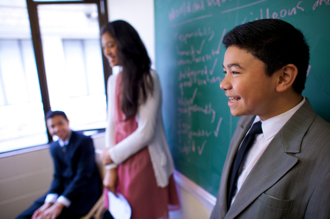 A young man in a suit stands in front of his Sunday School class with a young woman.