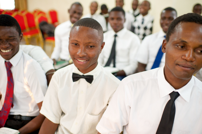 Young men from Africa sitting in rows at church, wearing white shirts, black pants, and ties, with red chairs in the background.