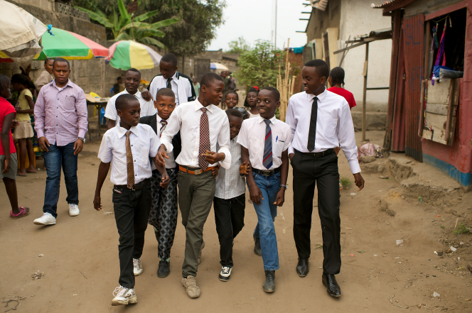 A group of young men in white shirts and ties, talking and walking down a village street together.