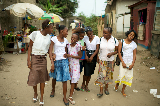 A group of young women in dresses and skirts, laughing and walking down a village street in Africa together.