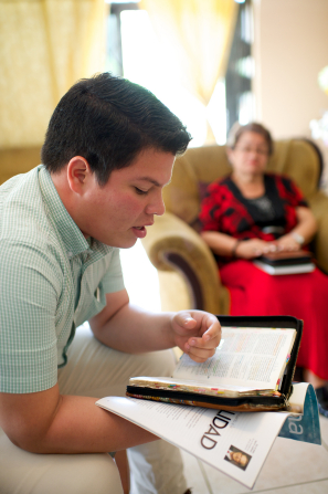 A young man from Ecuador sitting at home, reading from his scriptures and a Liahona magazine, with a woman sitting in the background.