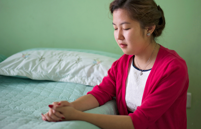 A young woman in a pink cardigan and a white shirt kneels down and rests her clasped hands on her bed to pray.