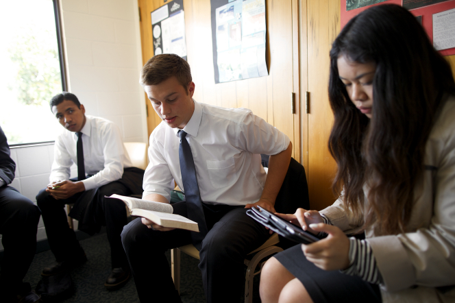 A young man reads from his scriptures during Sunday School. He is surrounded by two other young men and one young woman, who all read along with him.