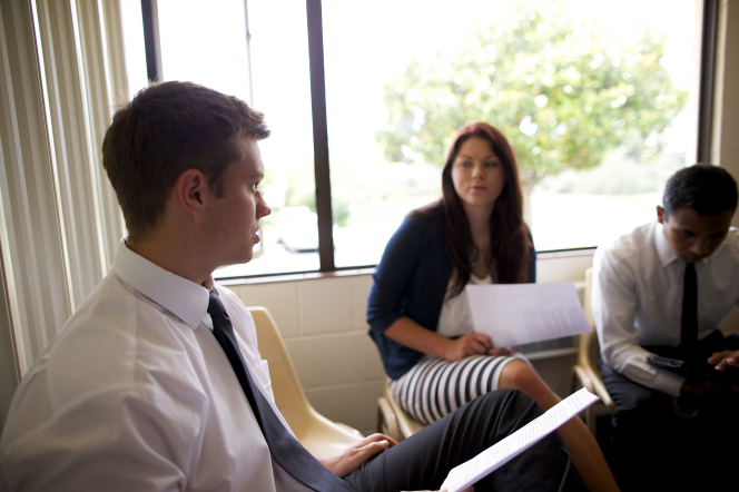 Two young men and a young woman sit and participate together in a youth Sunday School class.