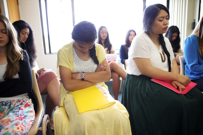 A group of eight young women in a classroom in New Zealand, all wearing skirts and dresses, fold their arms and close their eyes during prayer.